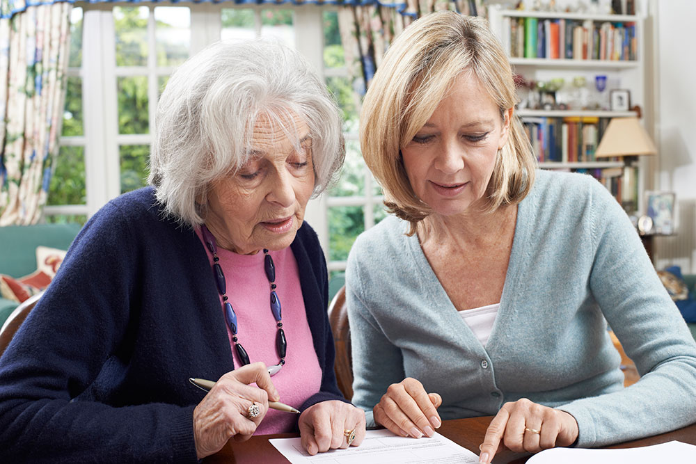 Adult Guardian helping a senior complete a form